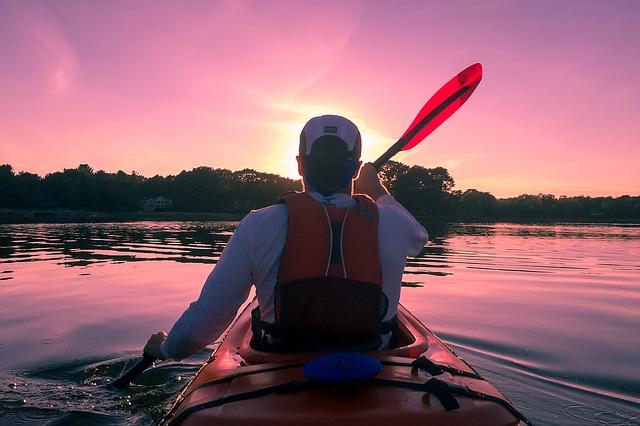 Man som paddlar kajak på västkusten i solnedgång