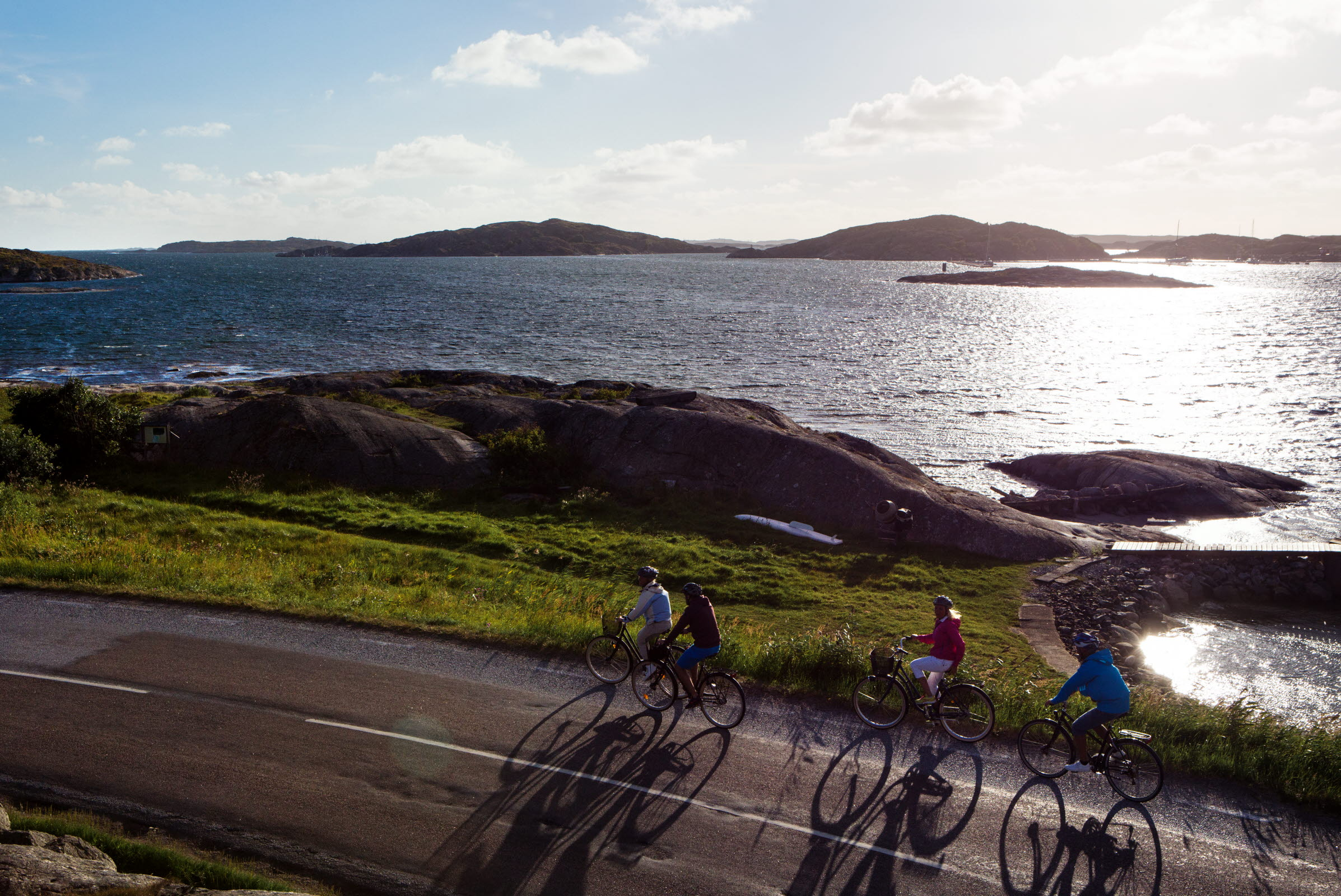 a group of people cycling along the sea on the west coast of Sweden