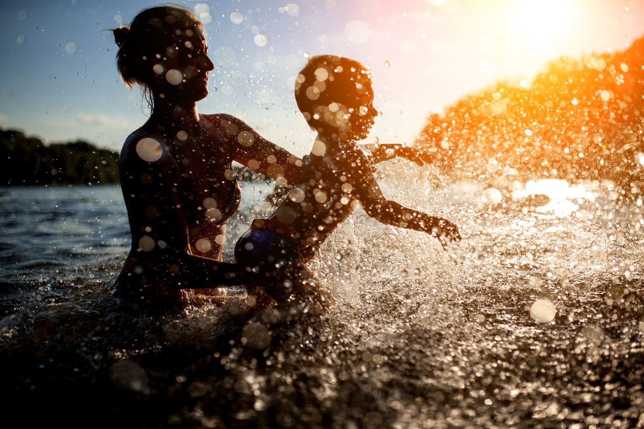 female with child bathe in lake or river and making water drops;
